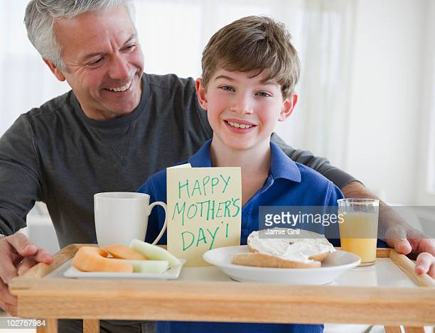 Father and son bring mom breakfast in bed