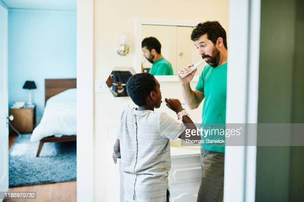 father and son brushing teeth in bathroom in home - modern manhood stock pictures, royalty-free photos & images