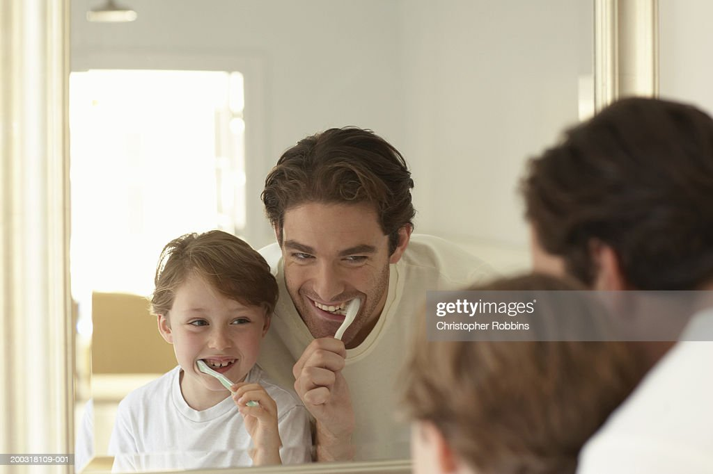 Father and son (5-7) brushing teeth, looking at reflections in mirror : Stock Photo