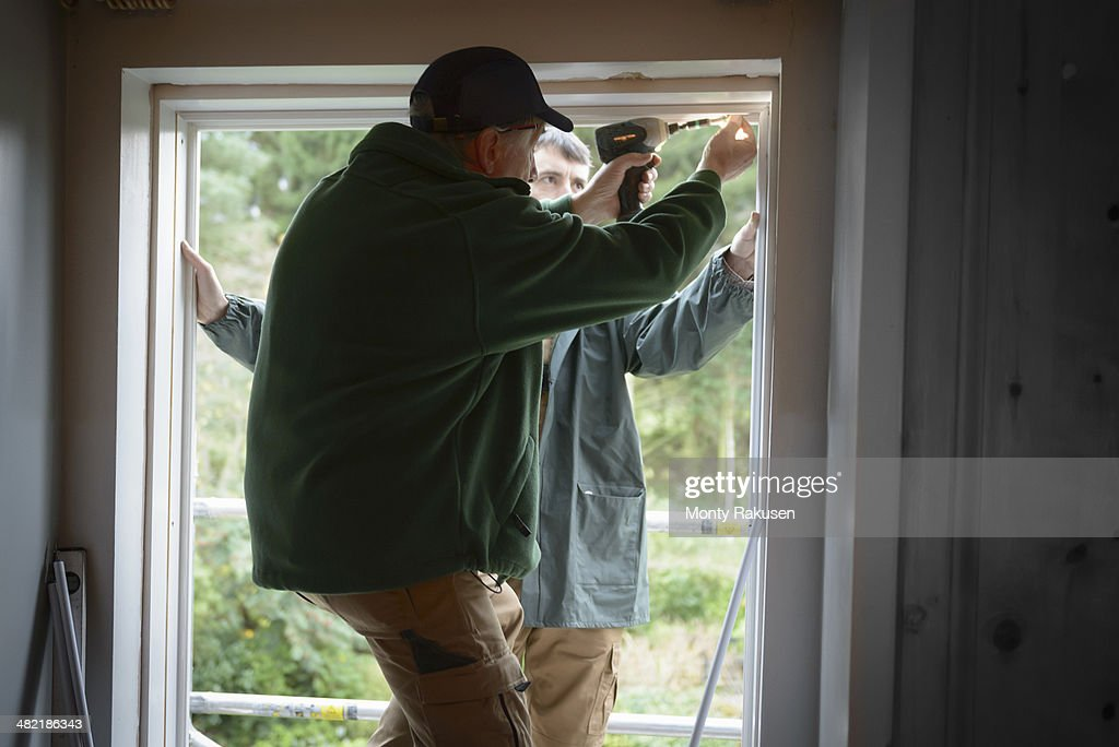 Father and son builders installing new window in house : Stock Photo