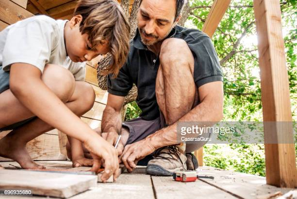 father and son building a tree house together - tree house stock pictures, royalty-free photos & images