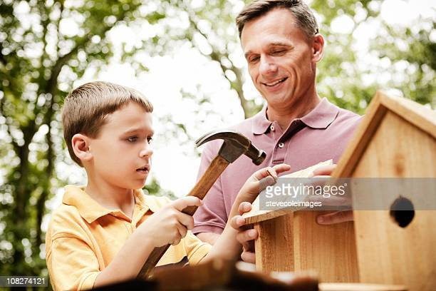 father and son building birdhouse - birdhouse stock pictures, royalty-free photos & images