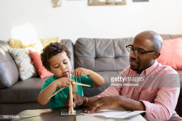 father and son building model windmill in livingroom - stroom activiteit stockfoto's en -beelden