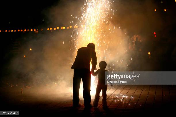 Father and son bursting fire crackers while celebrating Diwali Deepawali, festive-of-lights at Marine-Drive in Bombay