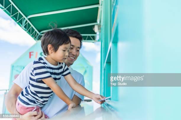 père et fils achète des billets d'entrée - hygiaphone photos et images de collection