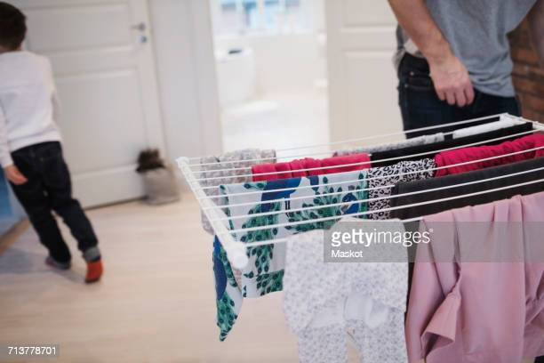 Father and son by clothes rack at home