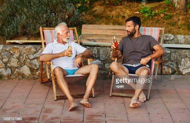 父と息子、プールサイド - アウトドアチェア ストックフォトと画像