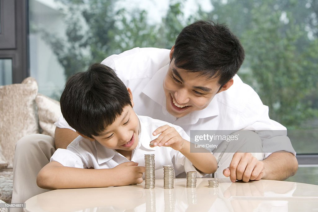 Father and son calculating coins : Stock Photo