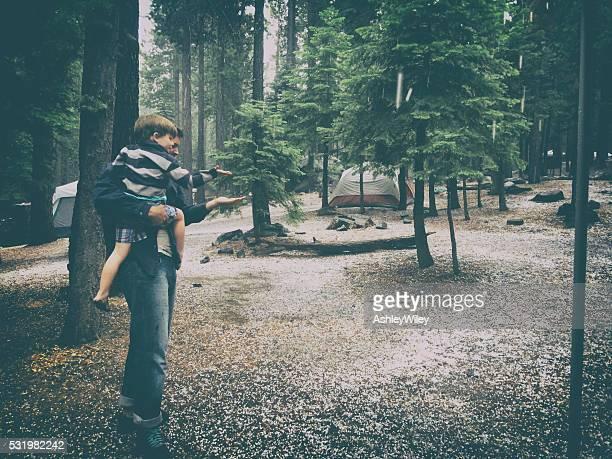 Vater und Sohn Camping in einen Hagel sturm