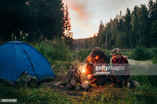 father and son camping together - campfire stock pictures, royalty-free photos & images