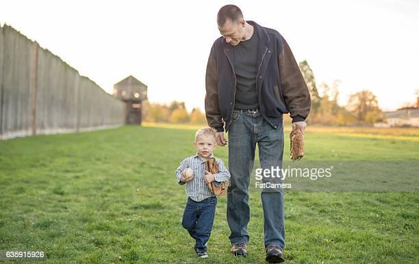 Father and son carrying baseball and mitt