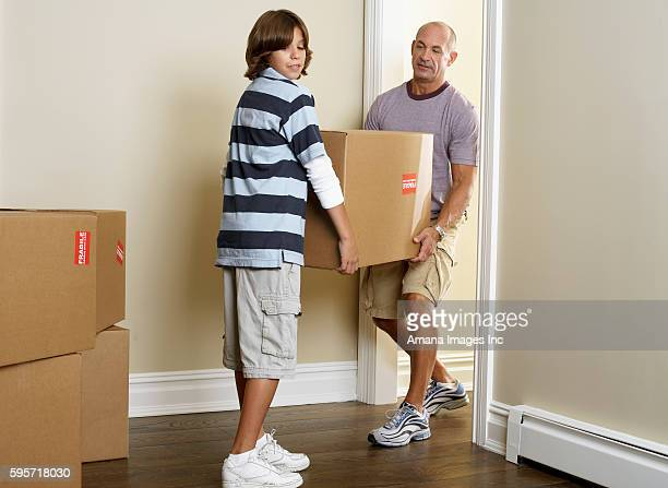 Father and Son Carrying Cardboard Box in Room