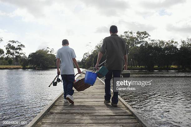 Father and son (10-12) carrying fishing gear on jetty, rear view