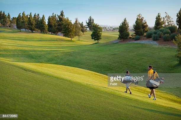 Father and Son Carrying Golf Club Bags