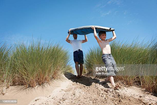 Father and Son Carrying Surf board