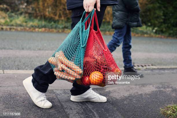 father and son carrying the food shopping home - sally anscombe stock pictures, royalty-free photos & images