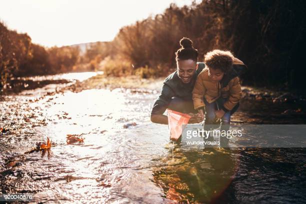 father and son catching fish with fishing net in river - sunset lake stock photos and pictures