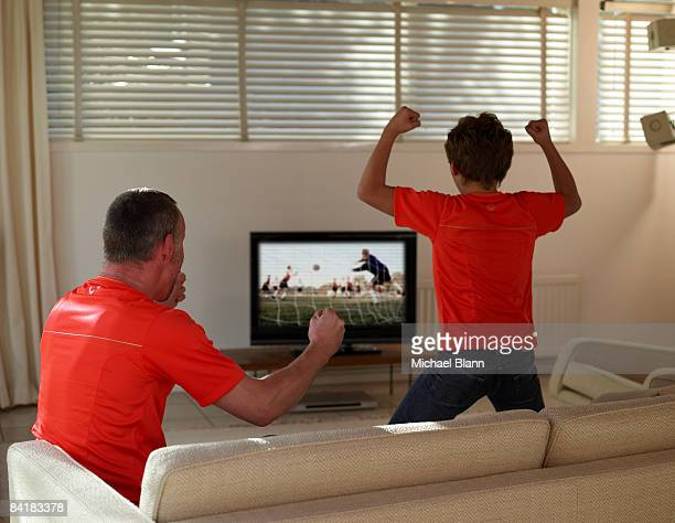 father and son celebrating a sport on TV at home