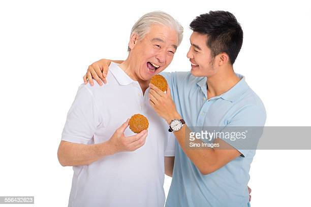 father and son celebrating mid-autumn festival - moon cake stock pictures, royalty-free photos & images