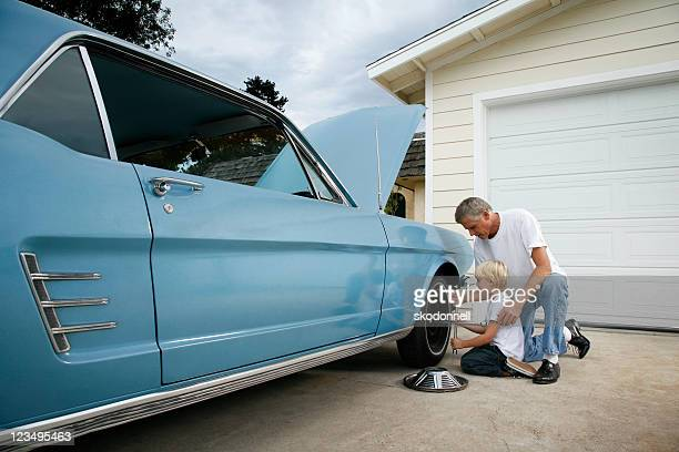 father and son changing a tire - vintage car stock pictures, royalty-free photos & images