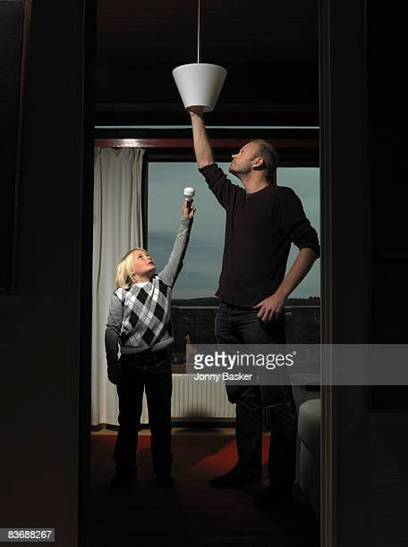 Father and son changing bulb