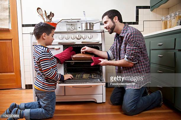 Father and son checking chocolate cake with toothpick
