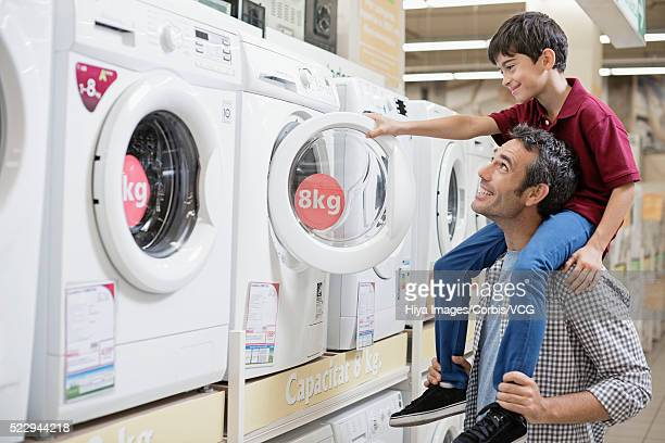 Father and son choosing washing machine in store