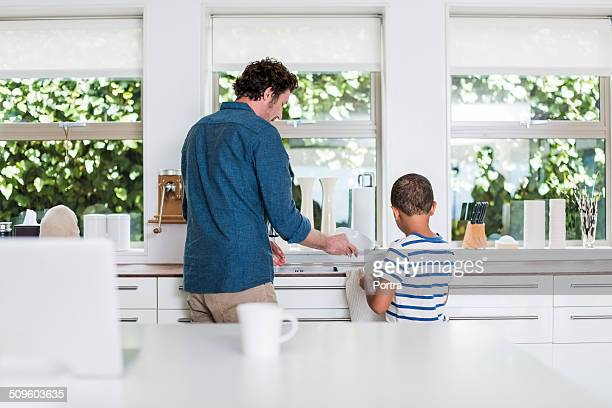 Father and son cleaning dishes in kitchen