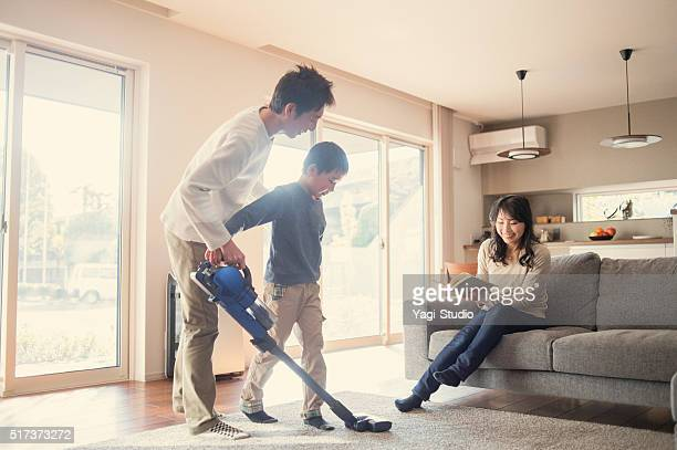 Father and son cleaning with a vacuum cleaner at home.