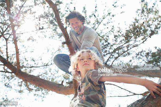 Father and son climbing tree
