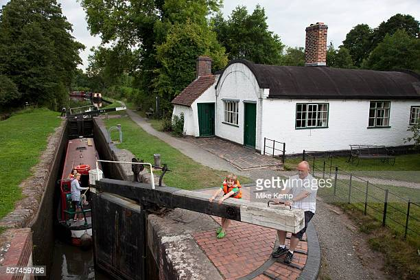 Father and son close a canal lock on the Grand Union canal at Lowsonford in Warwickshire The is lock is right beside a still functioning lock keepers...