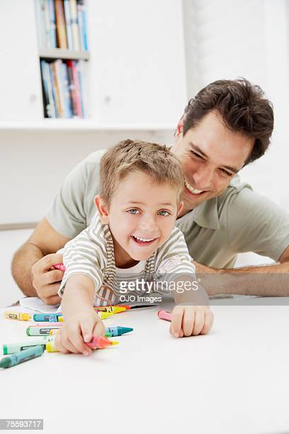 A father and son coloring together