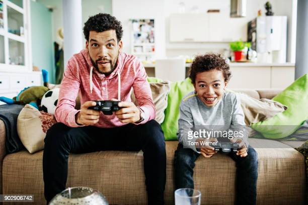 father and son concentrating while playing video games together - sohn stock-fotos und bilder
