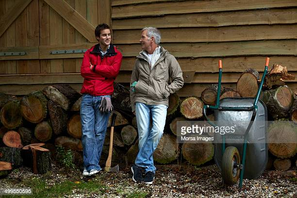 Father and son conversing against stacked firewood