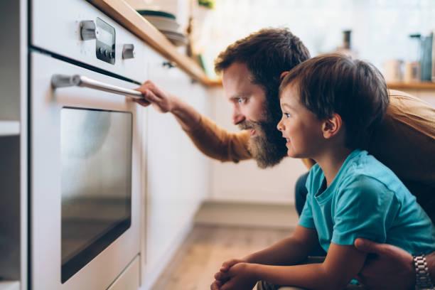 父親和兒子在家做飯 - 焗 預備食物 個照片及圖片檔