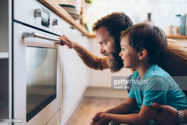 father and son cooking dinner at home - togetherness stock pictures, royalty-free photos & images