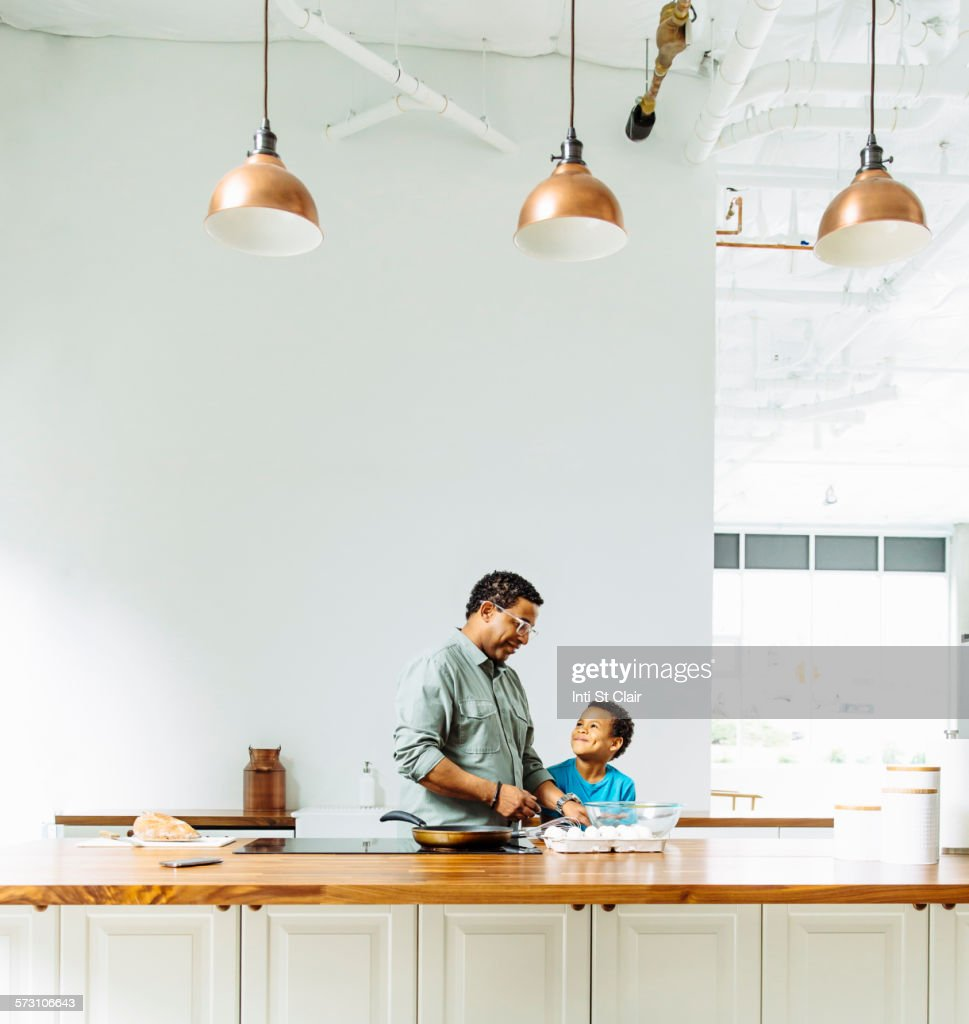 Father and son cooking in kitchen : Stock Photo
