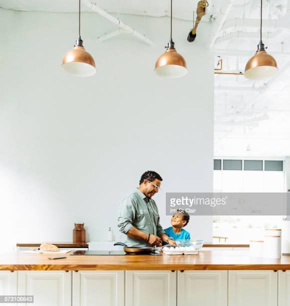 father and son cooking in kitchen - black cook fotografías e imágenes de stock