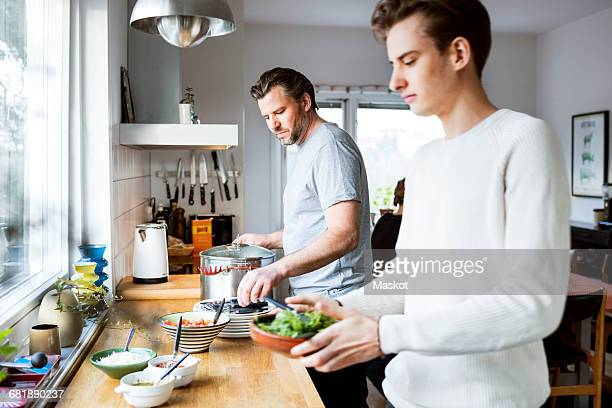 father and son cooking in kitchen - 20 24 years stock pictures, royalty-free photos & images