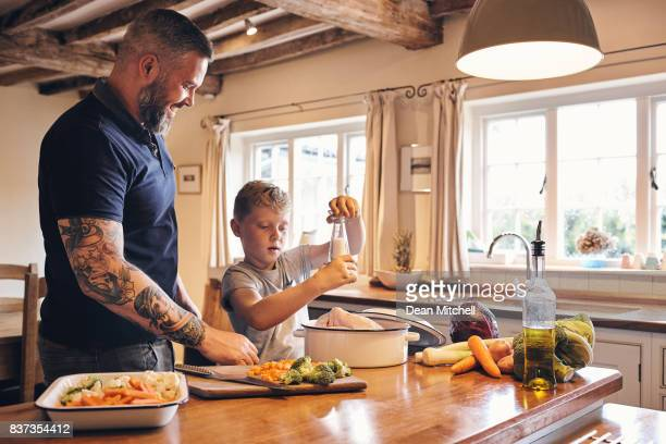 father and son cooking lunch in kitchen - single father stock pictures, royalty-free photos & images
