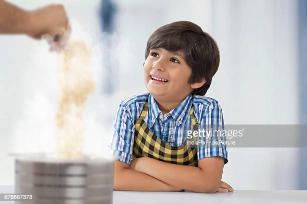 Father and son cooking noodles in kitchen