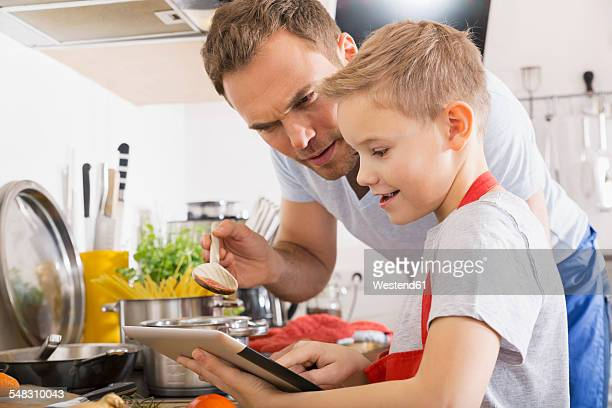 Father and son cooking together using digital tablet