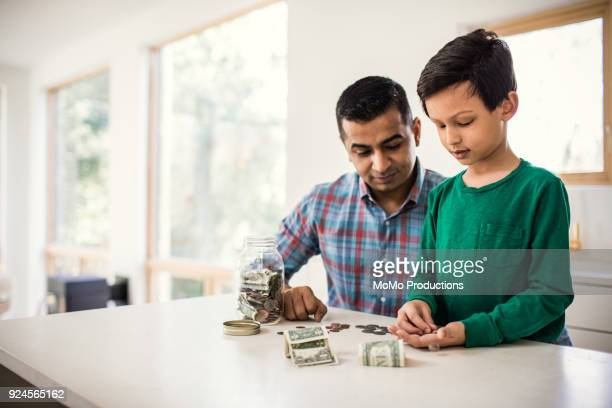 father and son counting money at home - savings stock pictures, royalty-free photos & images