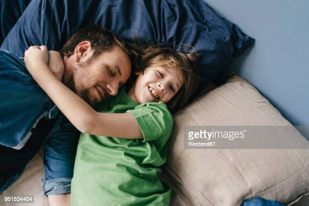 father and son cuddling at home - weekend activities stock pictures, royalty-free photos & images