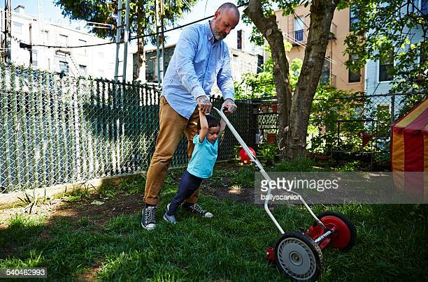Father And Son Cutting Grass In Garden.