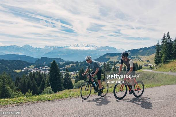 father and son cycling in french alps - france stock pictures, royalty-free photos & images