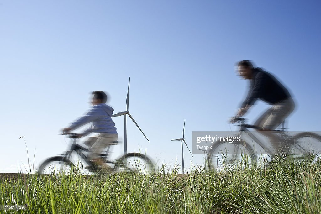Father and son cycling past a windfarm : Stock-Foto