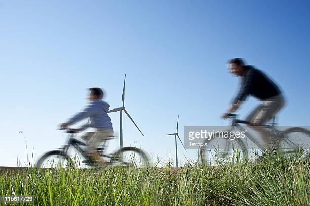 Father and son cycling past a windfarm