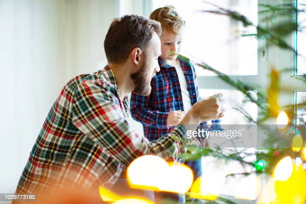 father and son decorating christmas tree - 2 5 months stock pictures, royalty-free photos & images