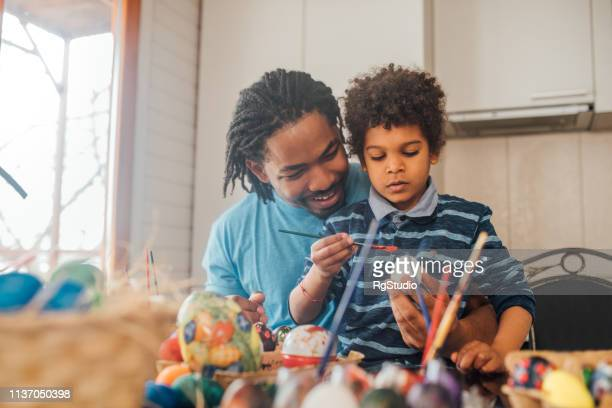 father and son decorating easter eggs - african american easter stock photos and pictures